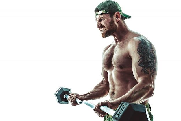 Homme musclé bodybuilder athlète en pantalon de camouflage avec un entraînement de torse nu avec haltère sur blanc