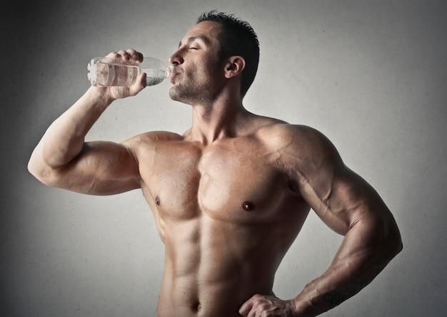 Homme musclé boire de l'eau