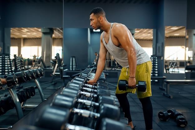 Homme musclé choisissant des haltères lourds sur l'entraînement en salle de sport