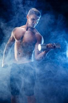Homme musclé concentré, faire des exercices avec haltère