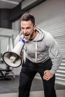 Homme musclé criant sur un mégaphone à la salle de gym crossfit