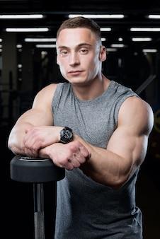 Un homme musclé dans une chemise sans manches grise pose appuyé sur une barre debout dans une salle de sport