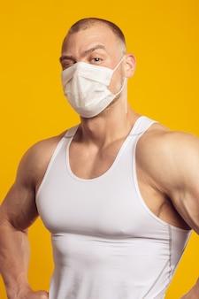 Homme musclé dans un masque médical et une chemise blanche, debout sur un mur jaune isolé