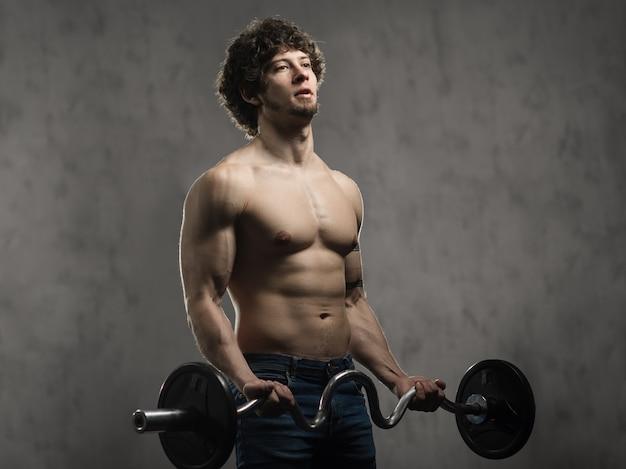 Homme musclé entraîne les biceps avec haltères dans la salle de sport, entraînement de la main
