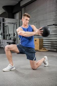 Homme musclé, entraînement avec médecine-ball au gymnase de crossfit