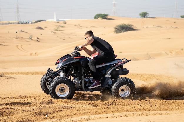 Homme musclé équitation vtt dans le désert