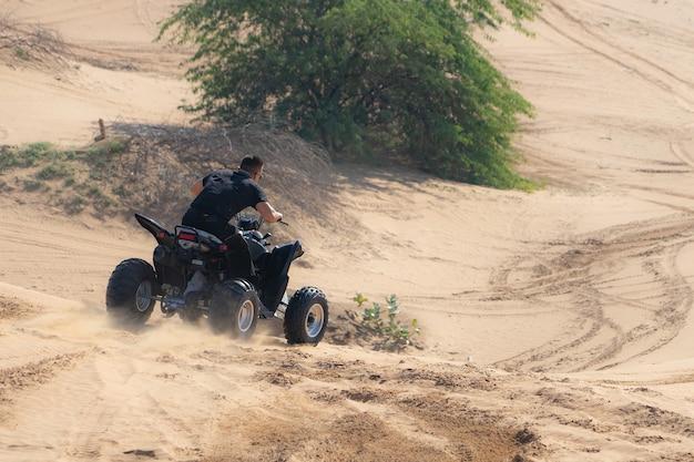 Homme musclé équitation vtt dans le désert.