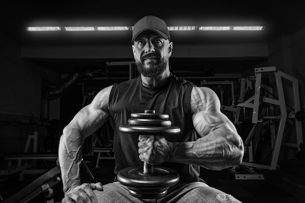 Homme musclé est assis sur un banc avec un haltère dans la salle de gym. concept de remise en forme et de musculation.
