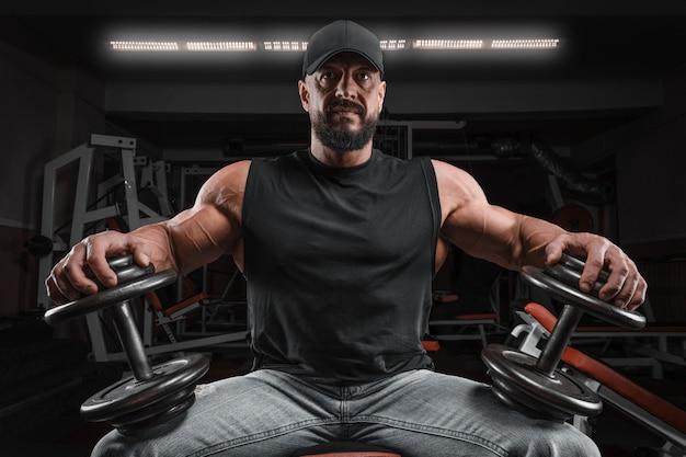 Homme musclé est assis sur un banc avec des haltères dans la salle de gym. concept de remise en forme et de musculation.