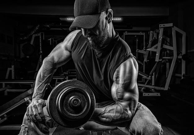 Homme musclé est assis sur un banc avec des haltères dans la salle de gym. pompage des biceps. concept de remise en forme et de musculation.