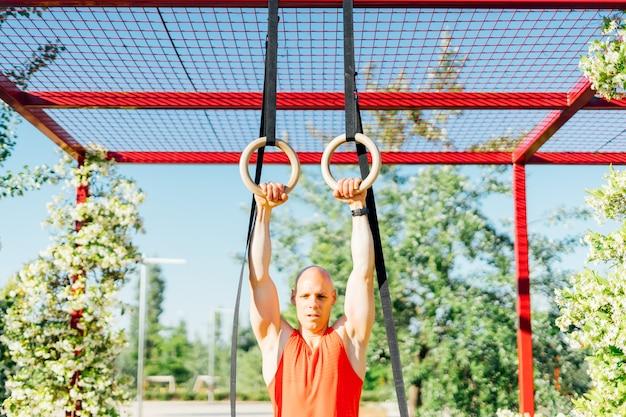 Homme musclé exerçant avec des anneaux.