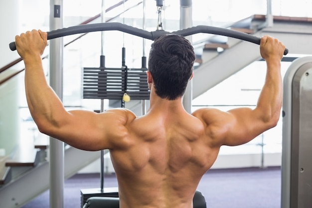 Homme musclé exerçant sur une machine de lat dans la salle de gym