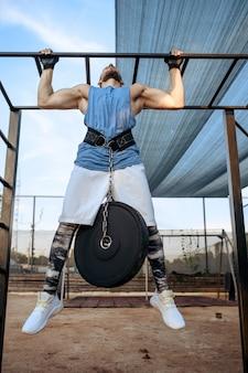 Homme musclé fait des exercices de tractions avec poids sur une barre horizontale