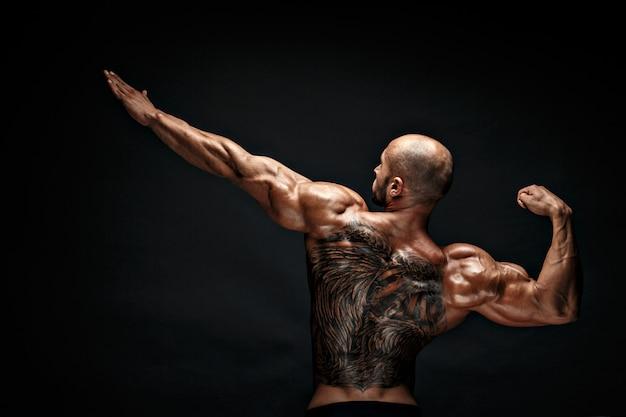 Homme musclé méconnaissable avec tatouage dos contre fond noir. isolé.