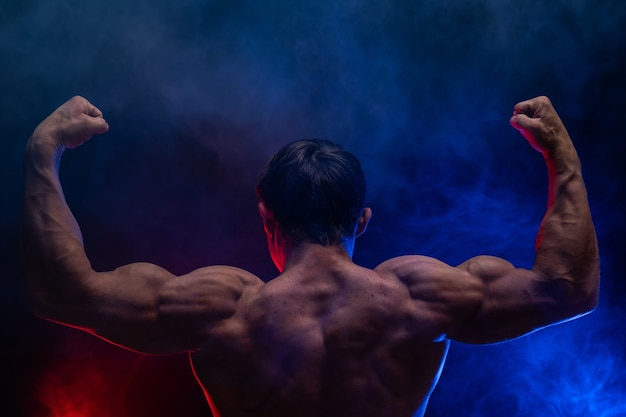 Homme musclé montrant des muscles isolés sur fond noir avec de la fumée colorée