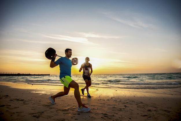 Homme musclé motivé accroupi avec barbillon au magnifique lever de soleil