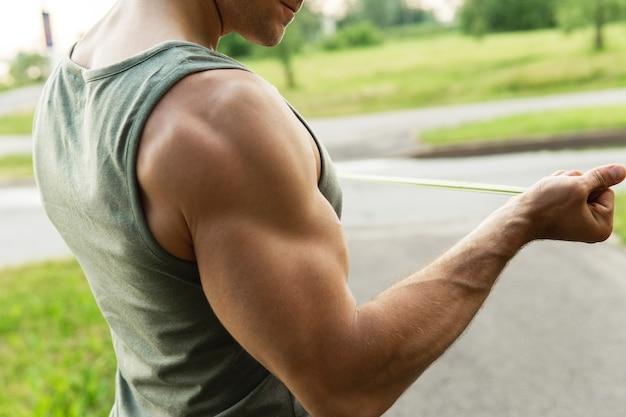 Homme musclé pendant l'entraînement avec des élastiques de résistance à l'extérieur.