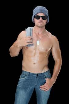 Homme musclé posant en chapeau bleu et des lunettes de soleil