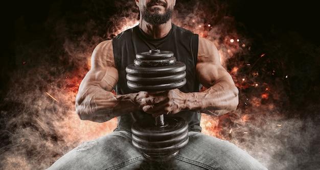 Homme musclé posant avec un haltère sur le feu et la fumée. concept de remise en forme et de musculation.