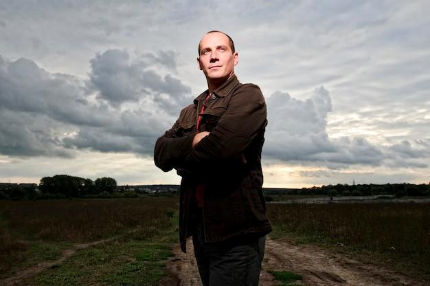 L'homme musclé pose à l'extérieur, toile de fond de ciel dramatique