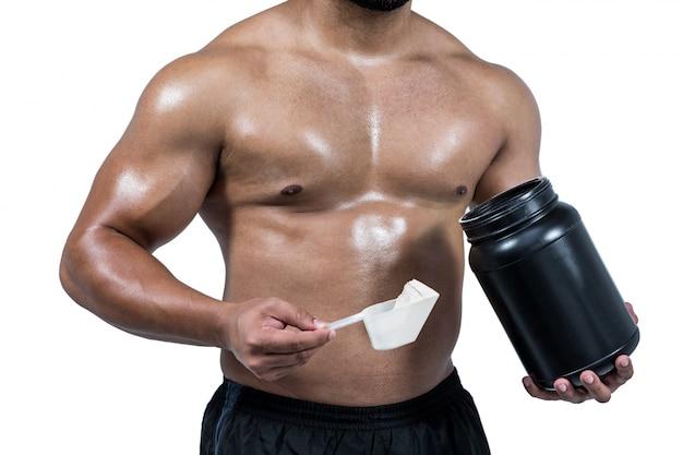 Homme musclé avec de la poudre de protéine