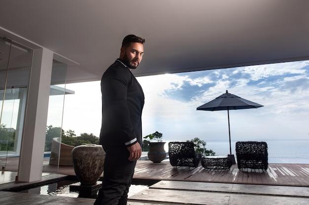 Homme musclé sérieux avec une barbe dans un costume d'affaires posant sur place