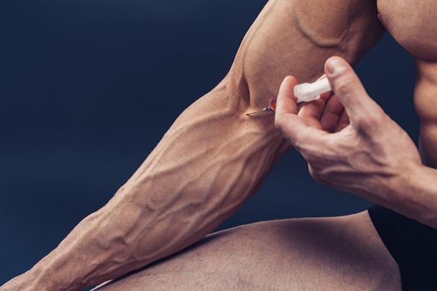Un homme musclé avec une seringue