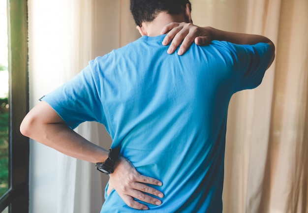 Homme musclé souffrant de douleurs au dos et au cou. problèmes de posture assise incorrects spasmes musculaires, rhumatismes. soulagement de la douleur, concept chiropratique. sport exercice blessure