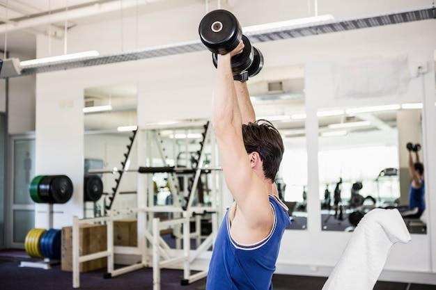 Homme musclé, soulevant des haltères sur un banc à la gym