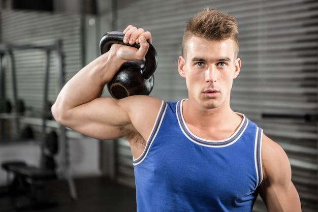 Homme musclé, soulevant lourd kettlebell à la gym crossfit