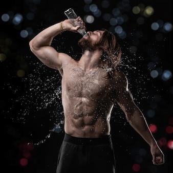 Homme musclé sportif buvant de l'eau en studio avec éclaboussures