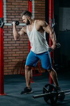 Homme musclé avec des tatouages et de la barbe faisant des biceps avec des haltères dans un débardeur blanc et un short bleu contre le mur de briques dans une salle de sport.