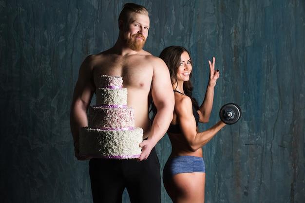 Homme musclé tenant un gros gâteau et une dame avec un haltère à la main