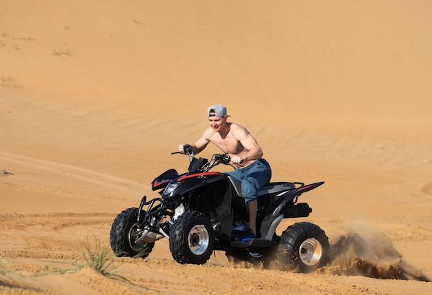 Homme musclé topless équitation atv dans le désert.