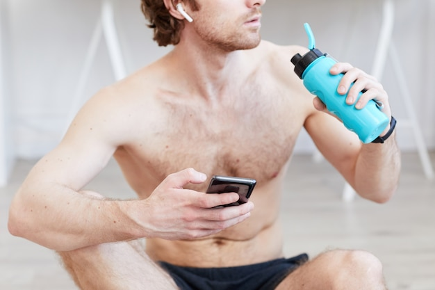 Homme musclé torse nu, boire de l'eau et utiliser son téléphone portable après l'entraînement sportif