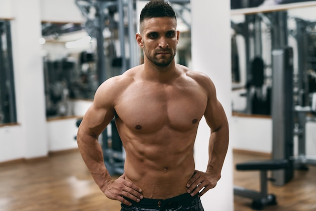 Homme musclé torse nu caucasien avec les mains sur les hanches posant dans une salle de sport