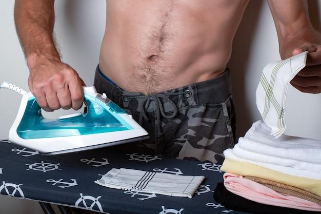 Homme musclé torse nu corps parfait repassage des vêtements sur la planche à repasser