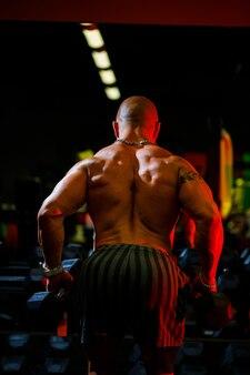 Homme musclé torse nu faisant des exercices d'haltères dans le cadre de son entraînement de musculation. motivation de remise en forme, mode de vie sportif, santé, corps athlétique, corps positif