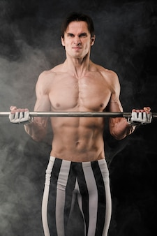 Homme musclé torse nu posant avec de la fumée et des poids