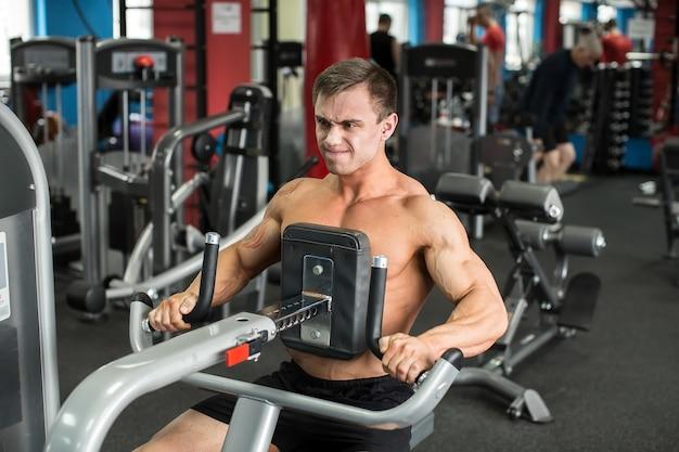 Homme musclé travaillant dans une salle de sport, faire des exercices, homme fort