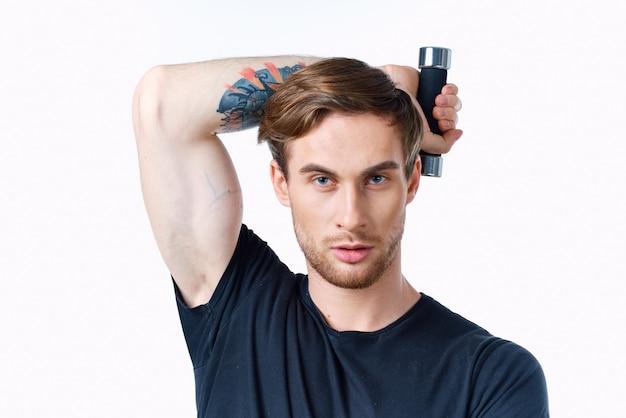 Homme avec des muscles du bras gonflés fitness entraînement t-shirt noir haltères. photo de haute qualité