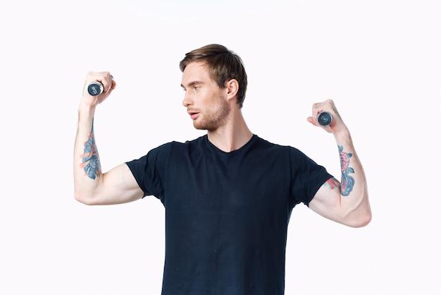 Homme avec des muscles gonflés des bras et des haltères tshirt noir blanc