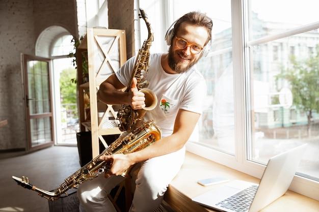 Homme musicien caucasien lors d'un concert en ligne à la maison isolé et mis en quarantaine,