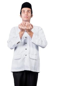 Homme musulman asiatique debout tout en levant les mains et en priant