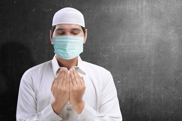 Homme musulman asiatique portant un masque de grippe debout tout en levant les mains et en priant