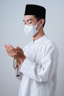 Homme musulman asiatique portant des vêtements musulmans tenant un chapelet avec masque médical