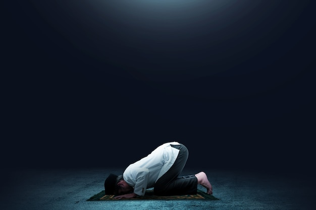 Homme musulman asiatique en position de prière (salat) sur un tapis de prière