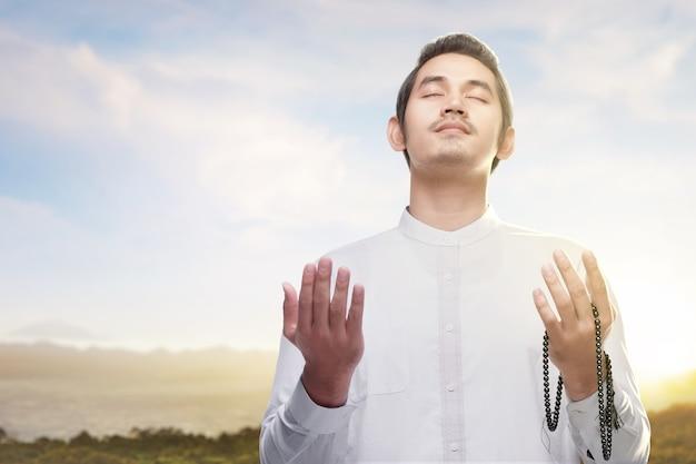 Homme musulman asiatique priant avec un chapelet sur ses mains