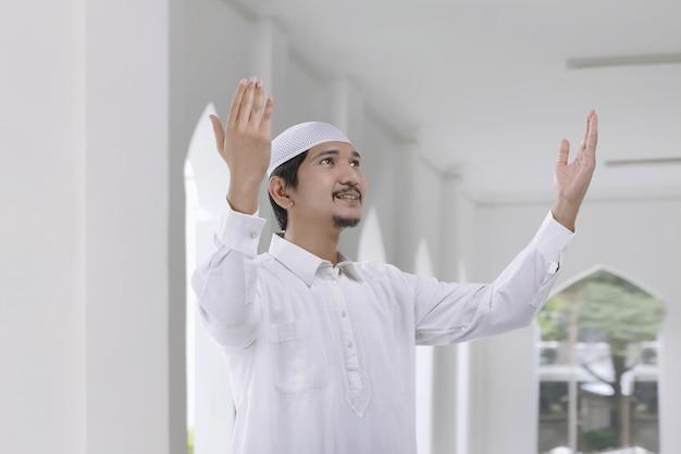 Homme musulman asiatique souriant avec une robe traditionnelle prier dieu