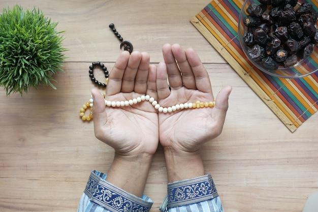 L'homme musulman garde la main dans les gestes de prière pendant le ramadan en gros plan